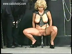 Master puts clamps with lots of weigh on pussy lips of granny slave with large pair
